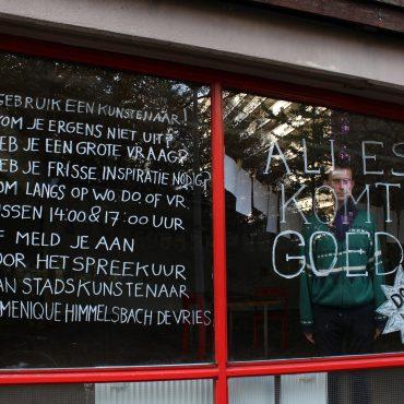 Sociaal kunstenaar Himmelsbach achter een raam met tekst die promoot om zijn performance actie residentie te bezoeken